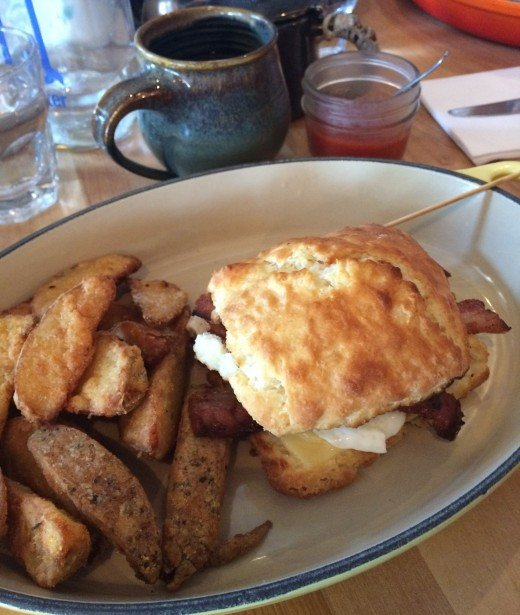 Mallard Cottage's Breakfast Sandwich with house-made bacon and wedges on the side.