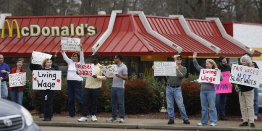 Protestors hold signs during a demonstration Thursday Dec. 5, 2013 on a sidewalk near the McDonald's on Brainerd Road in Chattanooga, Tenn. Demonstrators were taking part in a larger national campaign protesting low wages