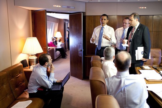 President Barack Obama meets with staff mid-flight aboard Air Force One