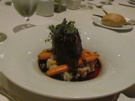 An elegant dish of short ribs surrounded by delicious veggies.