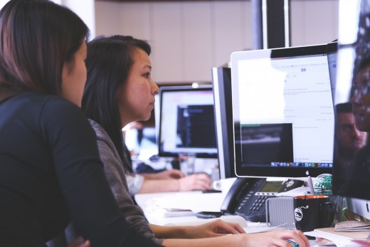 Women facing a computer.