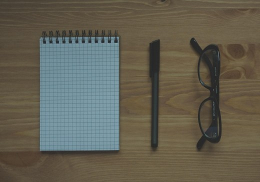 A notepad, pen, and glasses sit on a wooden table, shot from above.