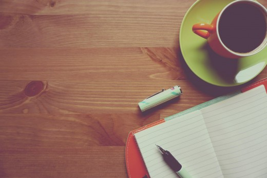 Wooden table, shot from above, with an orange mug on a green saucer, a notebook, and a pen and lid resting to the right.