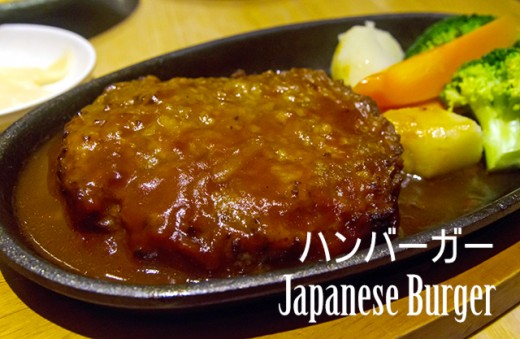 Japanese style burger on hotplate with brown sauce.