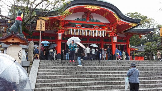 Main complex of Fushimi Inari Shrine, Kyoto. Constant flow of worshippers despite the rain.