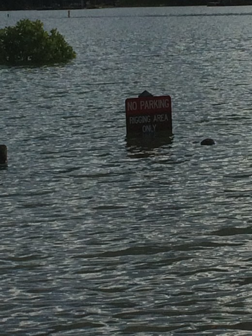 Park signs are almost buried in rising lake levels. The picnic tables are out there somewhere.