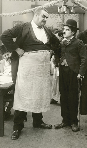 Charlie Chaplin playing the fool with giant waiter Eric Campbell.