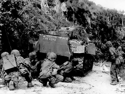 Marines take cover behind a tank during the Battle of Saipan