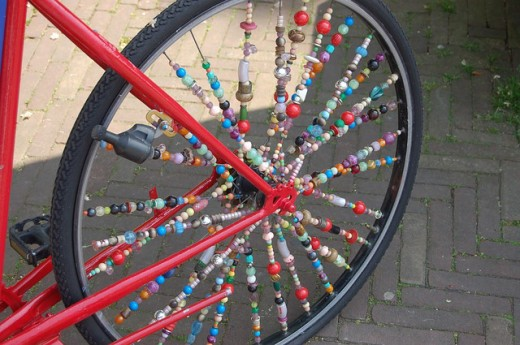 Decorated bicycle wheel of assorted beads.