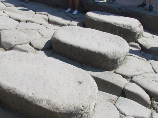 An example of what the streets were like in Pompeii where spaces were left between the rocks for the wheels of Roman chariots. They also had rocks and stones for stepping to avoid animal excrement as the horses pulled these chariots.