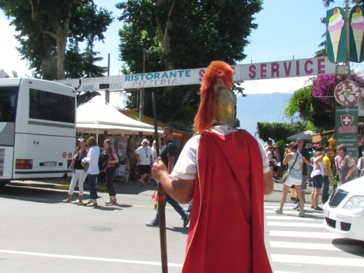A man dressed as a Roman Army Officer, stood in the square where various shops were in Naples.