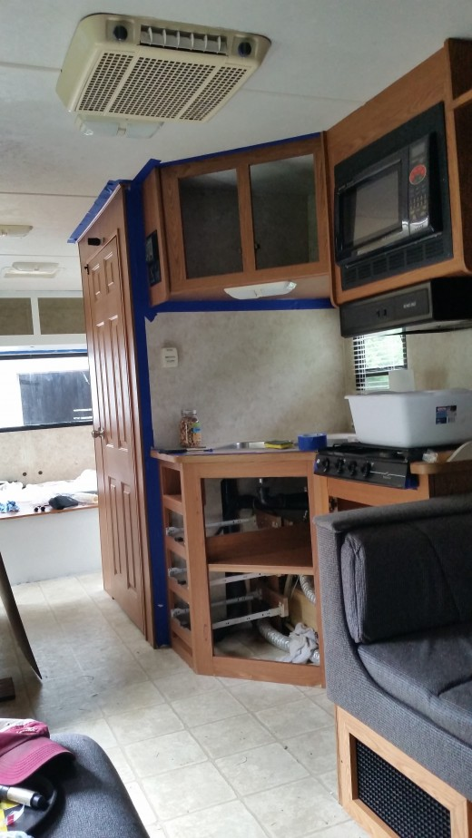 Kitchen with a semi view of the back bedroom with the primer on it.