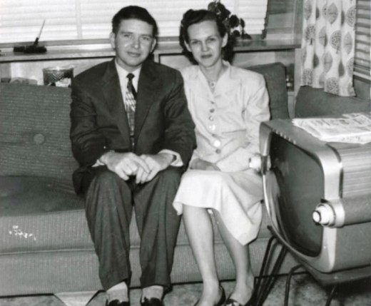 Newly wed couple from the fifties with their huge television set.