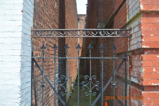 This Alleyway entrance still exhibits a beautiful section of wrought iron.