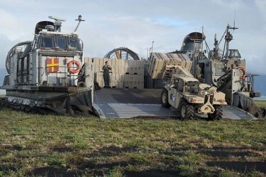 Material handling equipment such as the  Millennia Military Vehicle, seen off loading a USN Landing Craft Air Cushioned (LCAC), are present in USMC combat service support organizations.