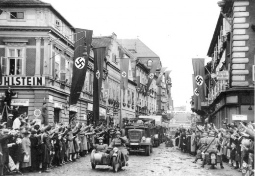 Ethnic Germans in Saaz, Czechoslovakia, greet German soldiers with the Nazi salute, 1938