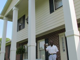 Randolph stands in front of his home in North Carolina, holding a photo of the tobacco markets that was burned during the riots in Mullins.