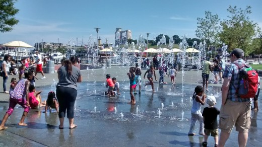 Children of different races enjoy playing at a water fountain in Baltimore at the Inner Harbor.
