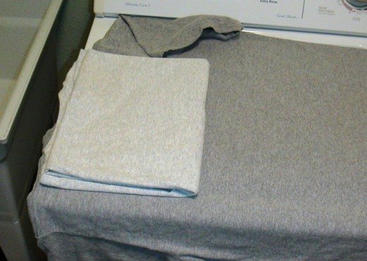 Fold the lower third of the shirt up toward the neck matching the edges.