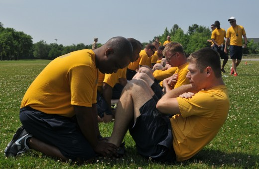 Sailors conducting curl-ups, a portion of the Navy PRT.