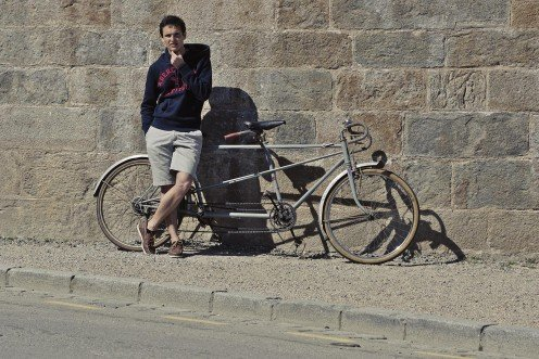 Guy looking cool posed with a bicycle