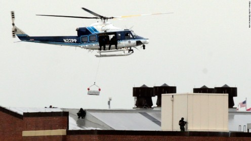 A police helicopter hovers above snipers on the roof  of a building in the  Washington Navy Yard  in a shooting rampage  where 12 were killed