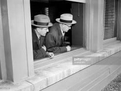Two Chicago officers in  the 1940s peer out of a  window pretending to be on a stakeout. Why? I do not know