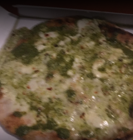 The pizza topped with pesto, another similar dish, always prepared by the local pizzeria. Pizza is less thin than focaccia (but always thinner than an American one)