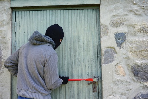 A thief committing burglary.