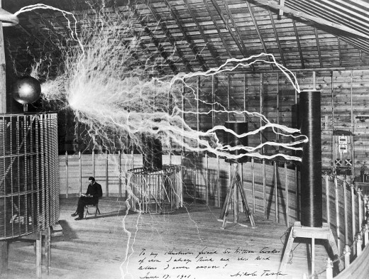 "Tesla in his laboratory in Colorado Springs around 1899, supposedly sitting reading next to his giant ""magnifying transmitter"" high voltage generator while the machine produced huge bolts of electricity. The photo was a promotional stunt."