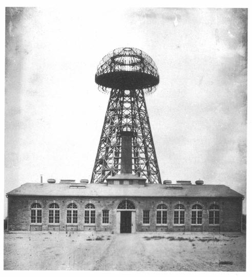 Nikola Tesla's Wardenclyffe wireless station, located in Shoreham, New York, seen in 1904. The 187 foot (57 m) transmitting tower appears to rise from the building but actually stands on the ground behind it.