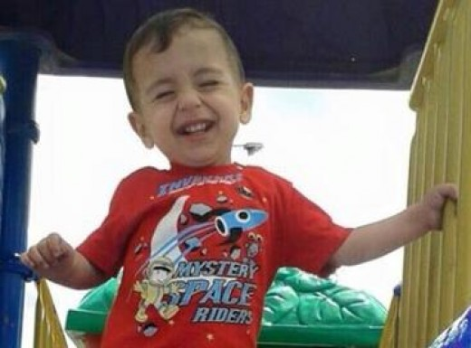 Alan Kurdi smiling in a playground