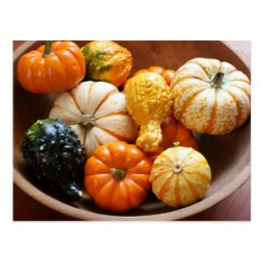 Assorted gourds and miniature pumpkins make a colorful display in a vintage wooden bowl.