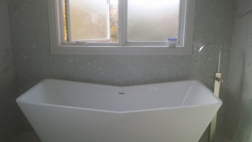 A gorgeous tub is easy to afford when you've painted on a marble look on the walls, rather than purchasing marble tile.