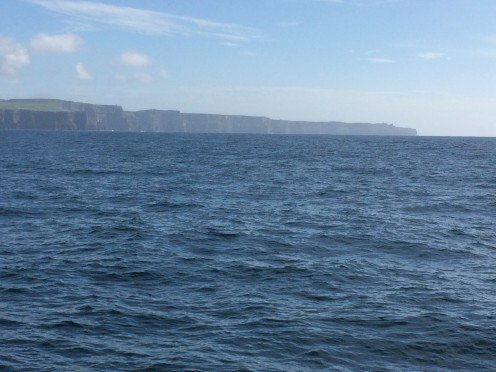 Distant view of the Cliffs of Moher from the water.