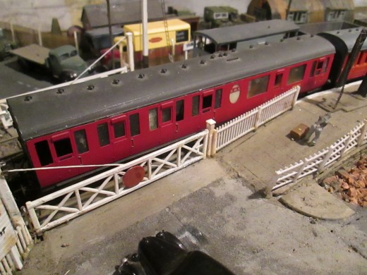 A better view of that first carriage as it rolls over the level crossing on its way down the branch. Thompson Lavatory Composite in early British Railways carmine livery. Note the oval 'Pullman'-type First Class toilet window.