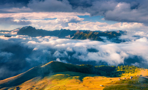 Sunny morning in the foggy Val di Fassa valley. View from Sella pass. Dolomite Alps, South Tyrol, Italy, Europe.