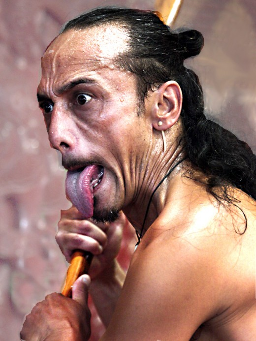 The tongue-poking face of a Maori warrior as he performs the haka