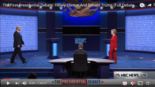 Both candidates are seen in frame; HRC's head is still downward, and DJT's head remains upright.  HRC is in front of her podium. DJT has not yet reached his podium.