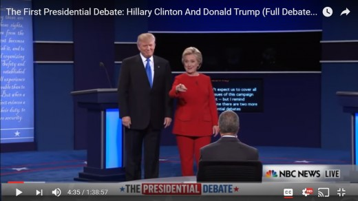 HRC points to someone in audience.  DJT stands still with arms by side.