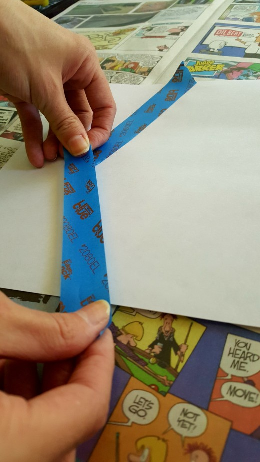 Creating a design. Remember to leave a little tape hanging off of the edge of your paper.