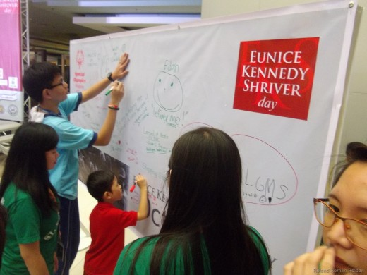 Athletes and guests writing message on the EKS Friendship Wall
