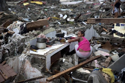 A woman searches amid the rubble of her home destroyed by Hurricane Matthew in Baracoa, Cuba