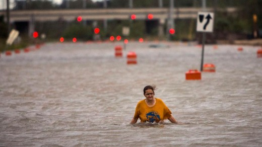 Homeless woman in Georgia wades through a flooded street