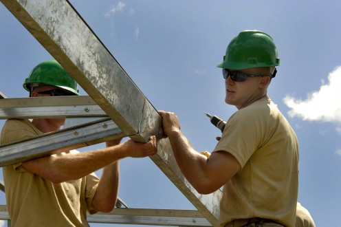 Construction workers installing a roof truss.