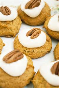 pumpkin cookies with vanilla icing topped with a pecan