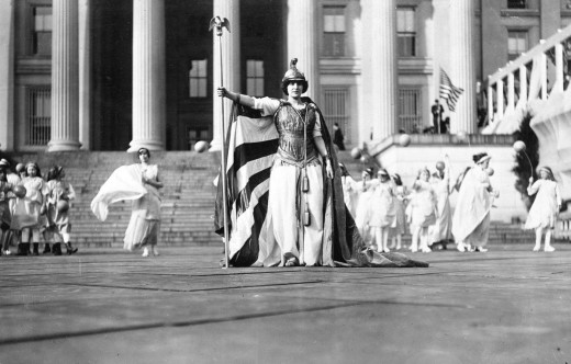 """At the parade, German actress Hedwig Reicher wore the costume of """"Columbia"""" with other suffrage pageant participants wearing white stood in background in front of the Treasury Building."""