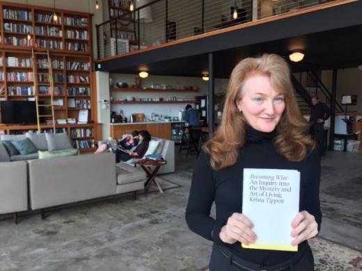 Krista Tippett holding a copy of her book.