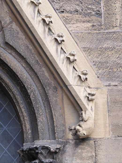 Relief of the fall of a devil on a lateral entrance on the facade of the Saint-Martin cathedral in Colmar, France.
