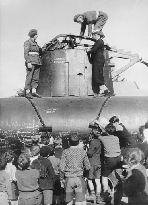 Melbourne, Vic. School children and service personnel inspect the mid-section of a Japanese midget submarine on display in the exhibition gardens. This submarine took part in the unsuccessful attack on Sydney harbour on 31 May 1942.